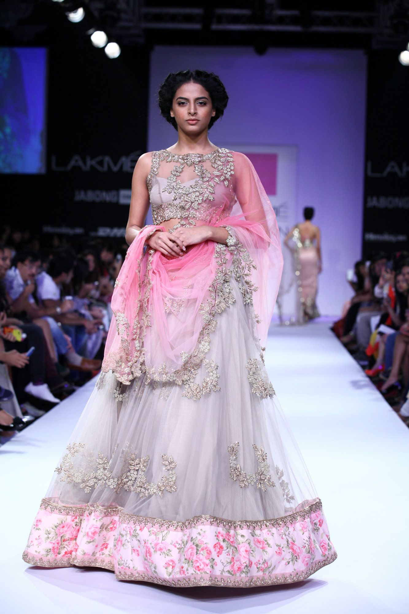 a model on the runway in a grey and pink lehenga