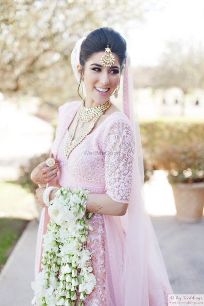 a bride in a pastel pink lehenga with orchid kaleeras