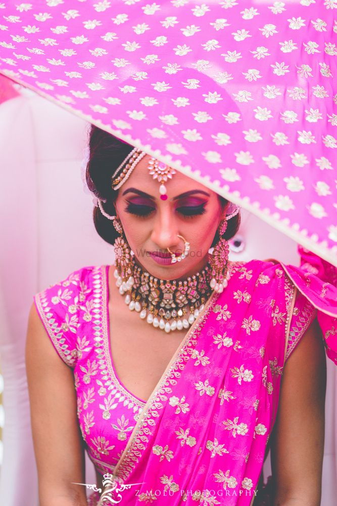 Photo of Dupatta placing on head shot with bright pink lehenga
