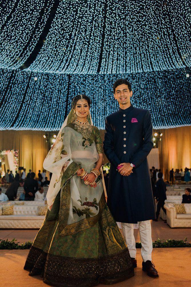 Photo of Contrasting bride and groom with Sabyasachi lehenga