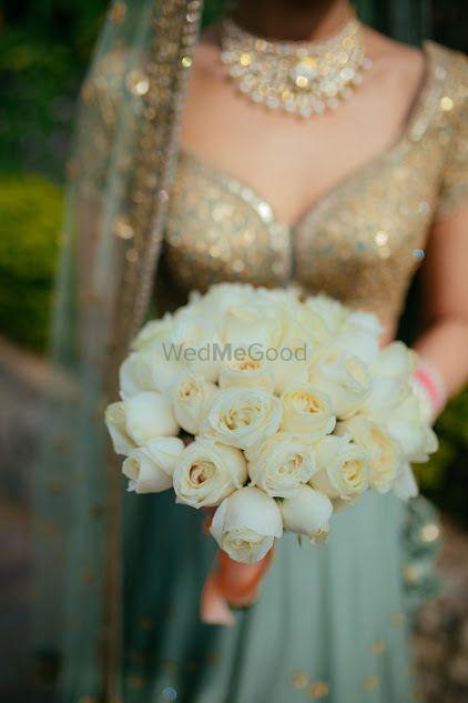 Photo of Bride in lehenga holding bouquet