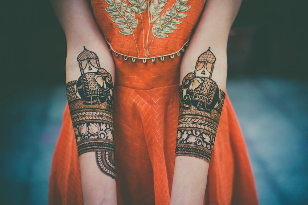 Photo of A bride shows her mehendi to the camera
