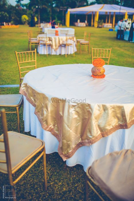 Photo of gold foil metallic table centerpiece with gold chairs