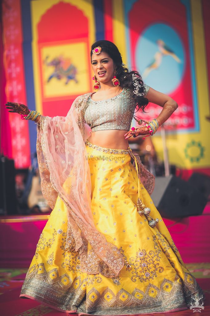 Photo of Mehendi lehenga in yellow on dancing bride
