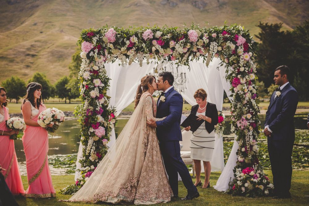 Photo of Bride and groom kiss at wedding
