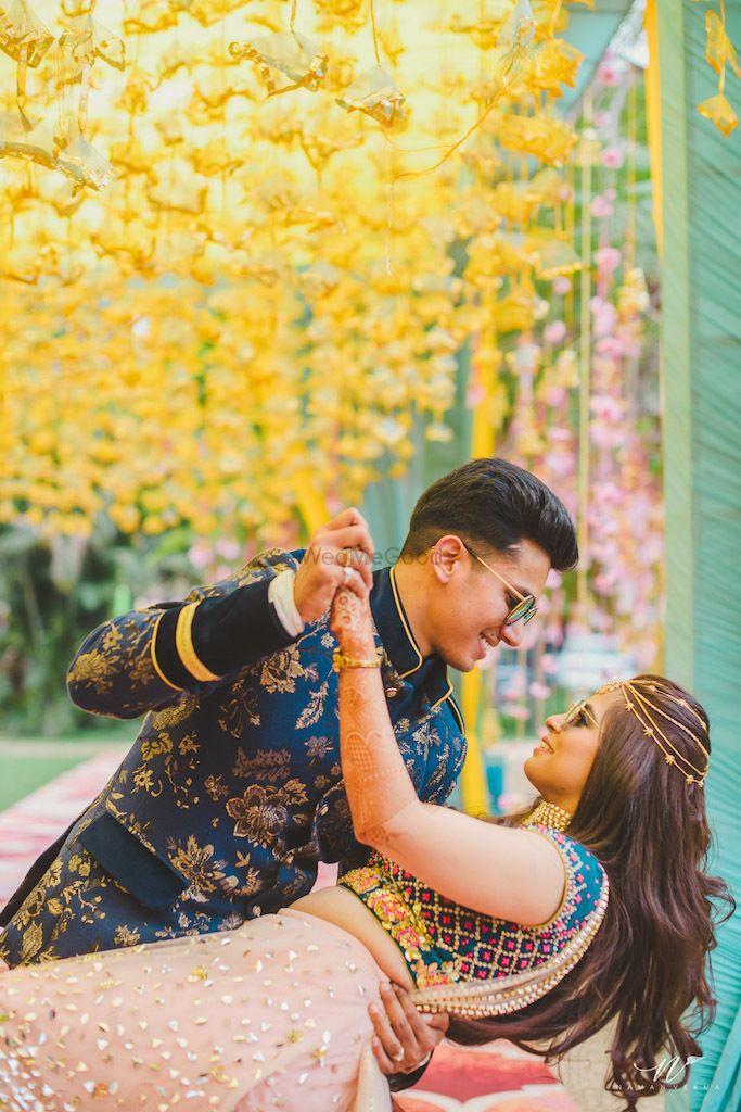 Photo of Mehendi couple portrait idea against yellow floral strings