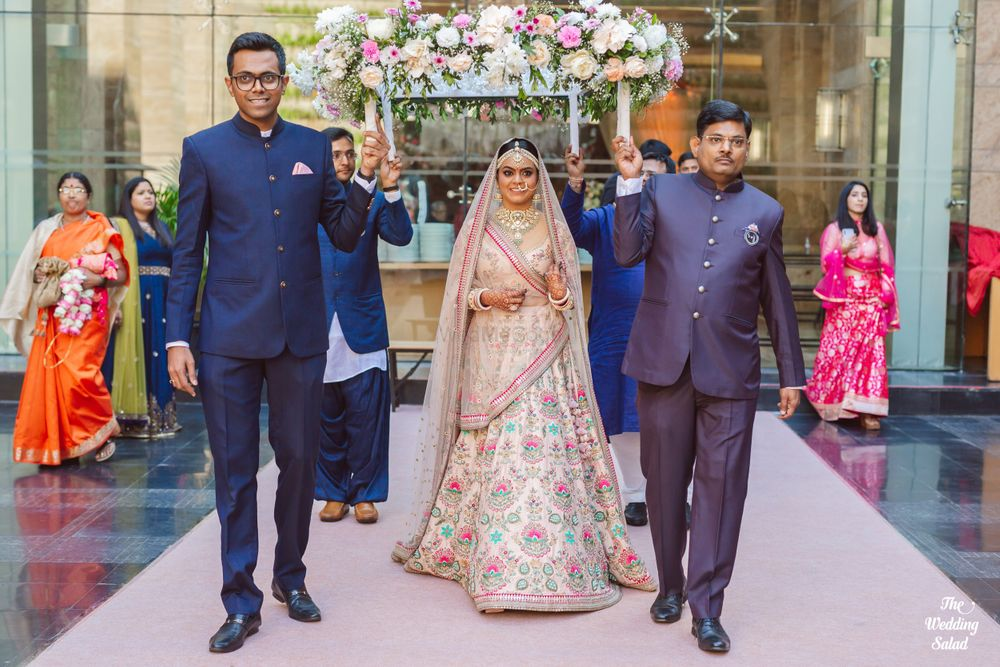 Photo of pastel pink sabyasachi bride entering under phoolon ka chadar