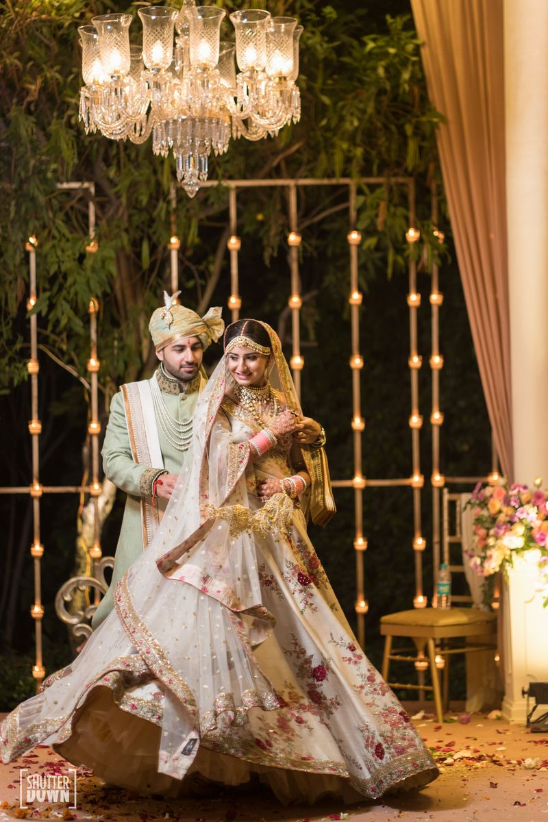 Photo of Couple portrait with twirling bride in floral print lehenga