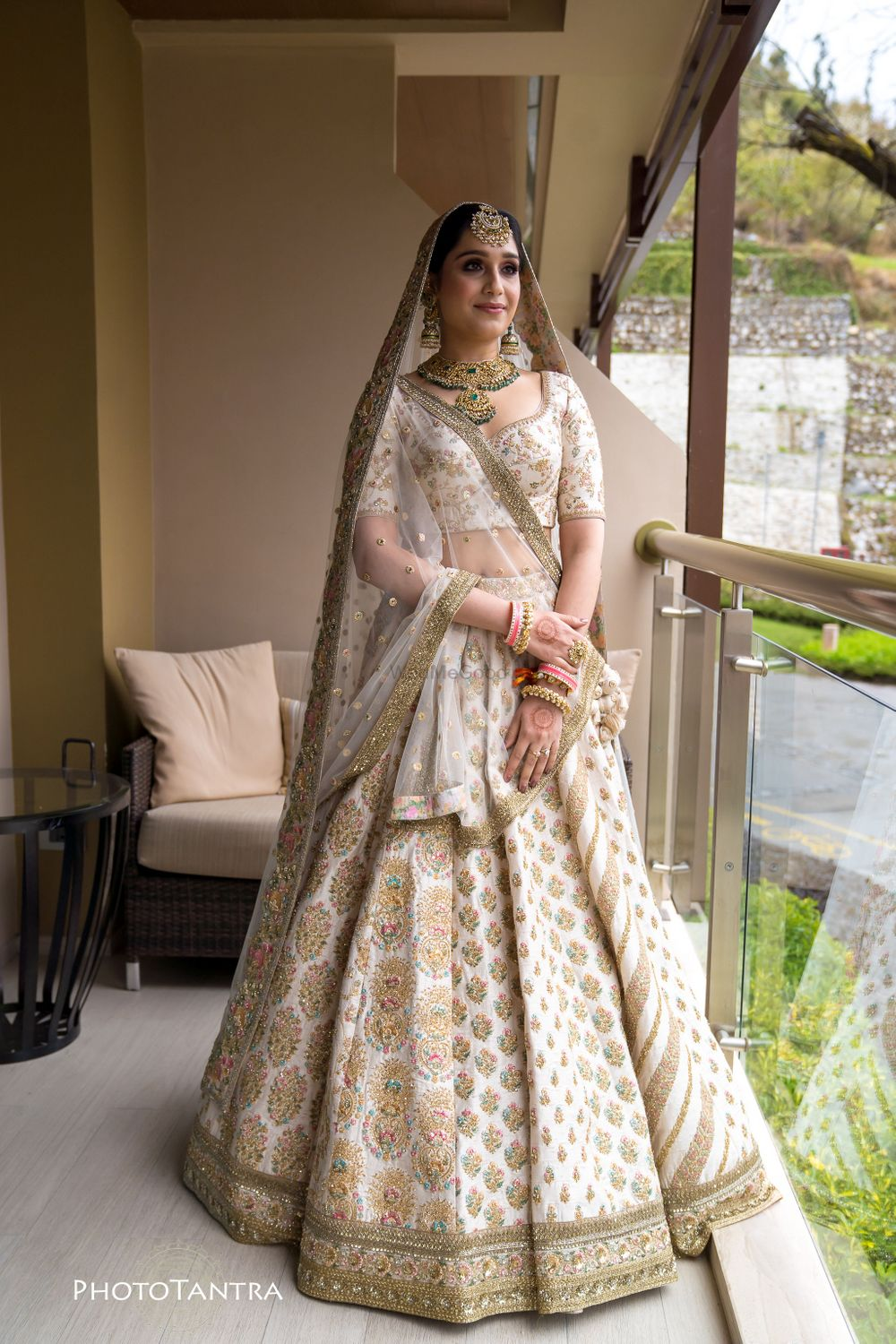 Photo of A bride in an ivory and gold lehenga with contrasting jewellery