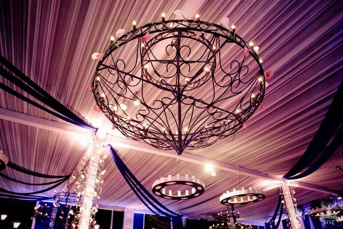 Photo of glamorous ceiling decor with wrought iron chandeliers and candles