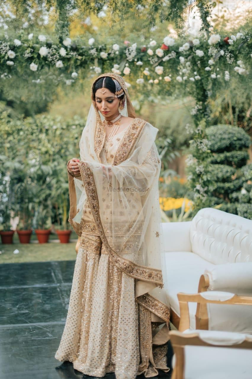 Photo of Bride wearing a white and gold sharara set on her wedding day.