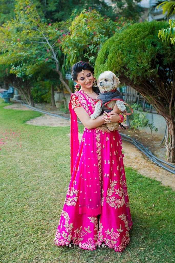 Photo of Bride in bright pink lehenga with dog