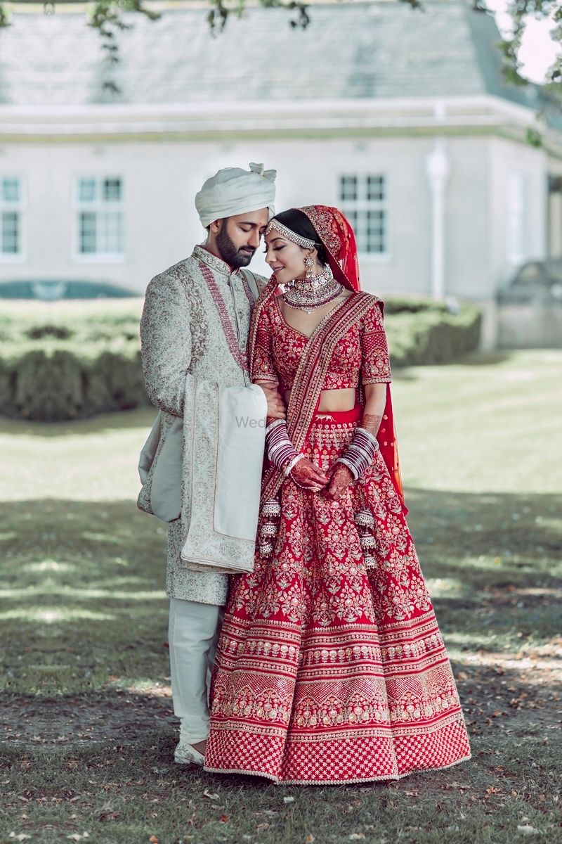 Photo of Bride and groom color-contrasting in red and white