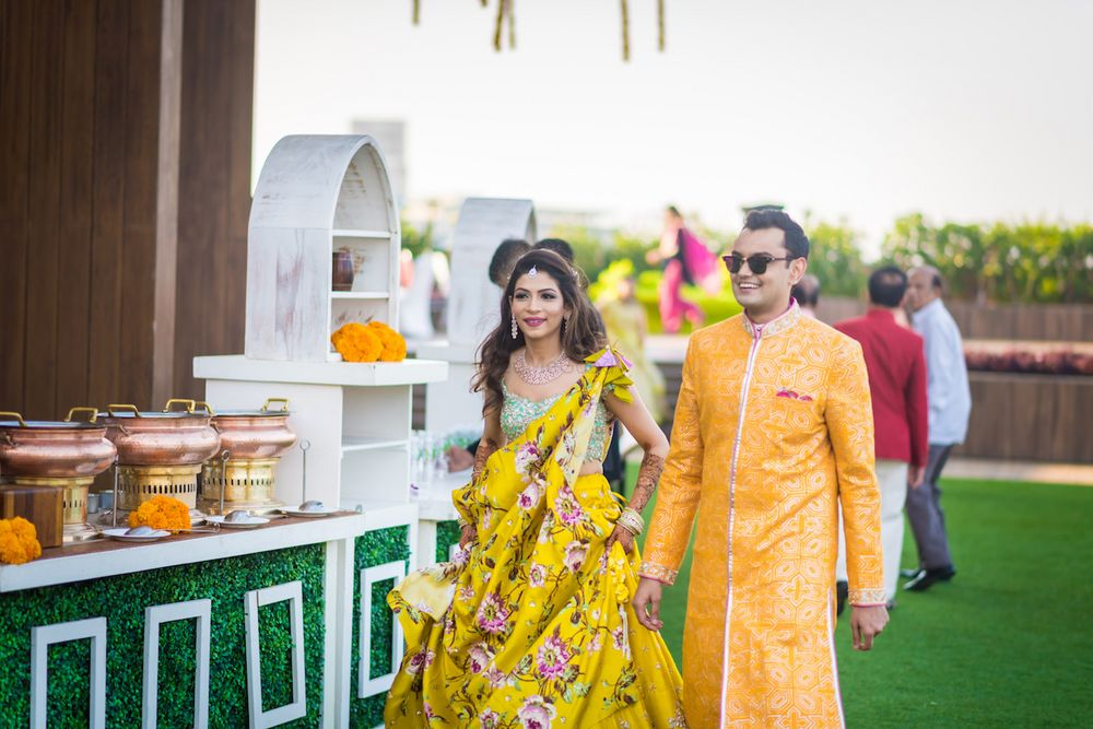 Photo of A bride and groom to be in yellow at their mehendi function