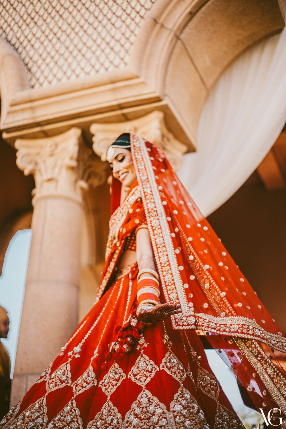 Photo of Wedding day bridal portrait in her red and gold sabyasachi lehenga