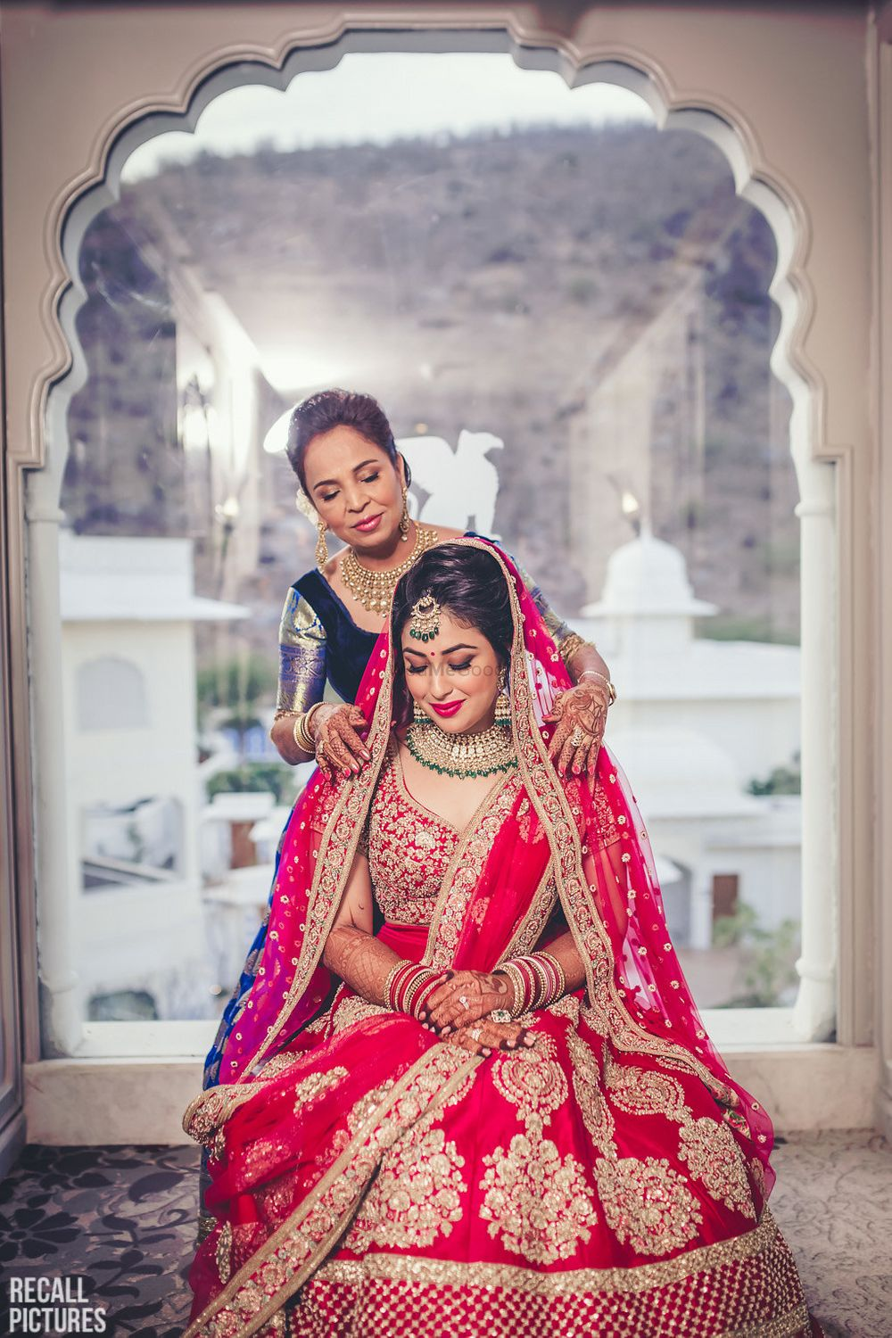 Photo of Brides mom placing the red dupatta on her head