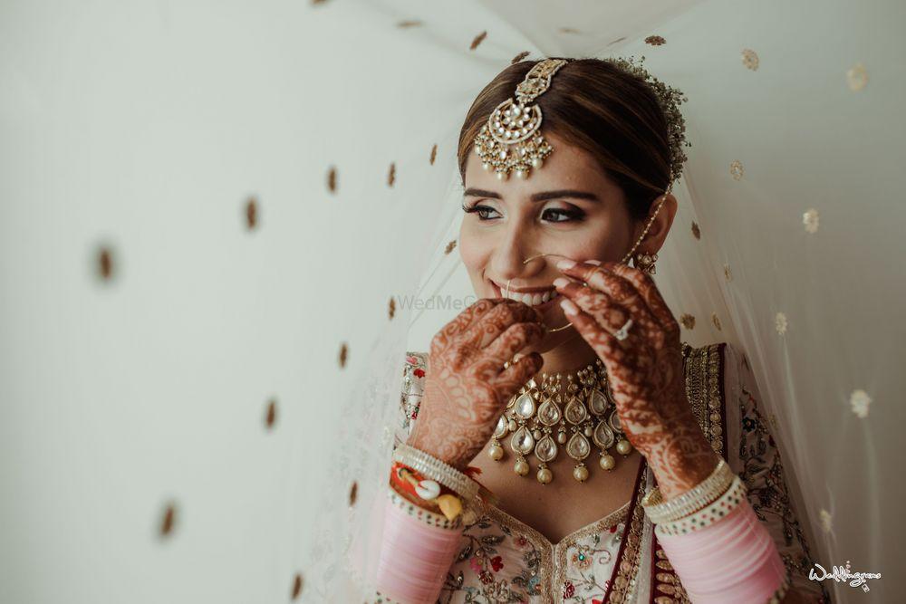 Photo of under the veil shot with bride adjusting her nosering