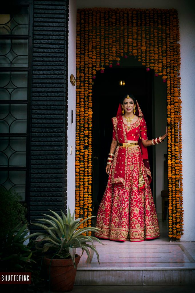 Photo of Red and gold bridal lehenga with waist belt