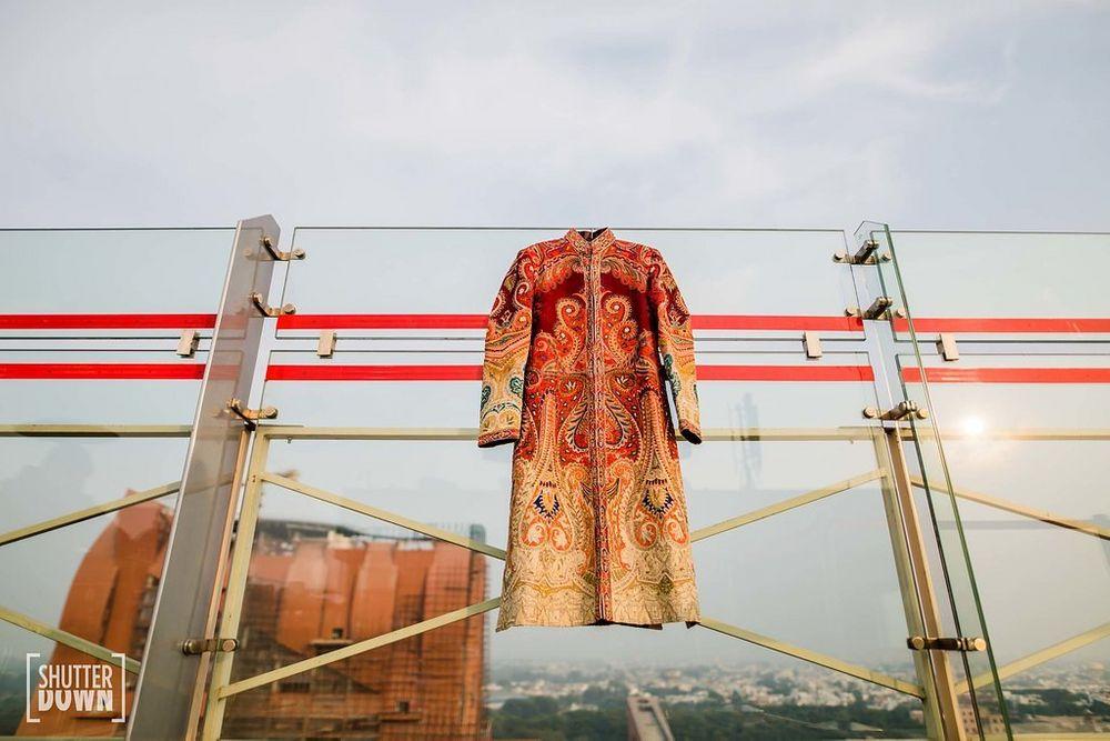 Photo of Orange sherwani on hanger