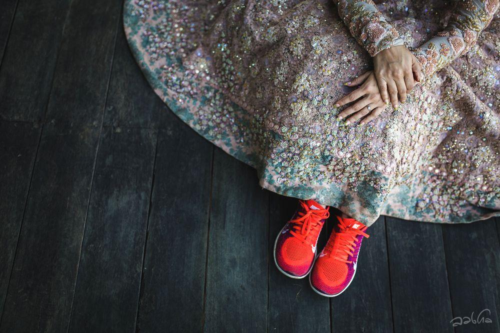 Photo of Bride wearing red sneakers under bridal lehenga