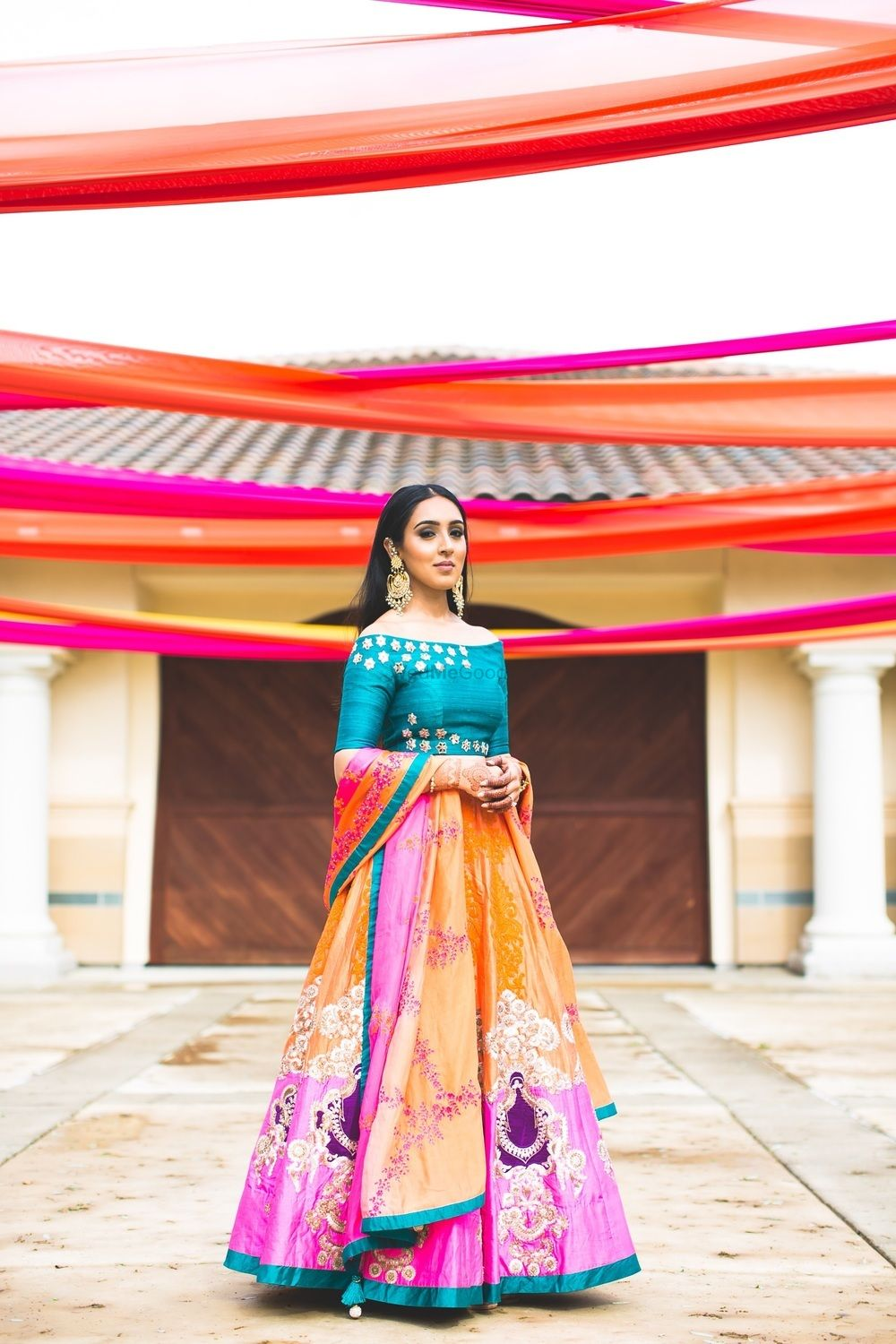 Photo of Quirky mehendi lehenga with teal off shoulder blouse