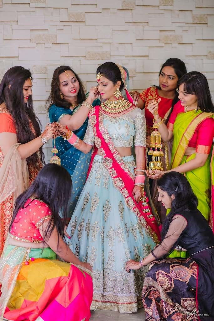 Photo of A bride in blue lehenga wit her bridesmaids
