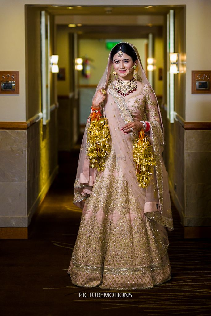 Photo of Light pink and gold bridal lehenga with kaleere