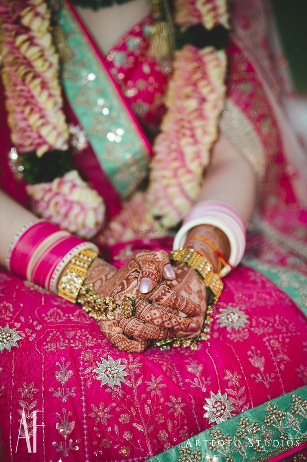 Photo of Bridal hands with green and gold haathphool