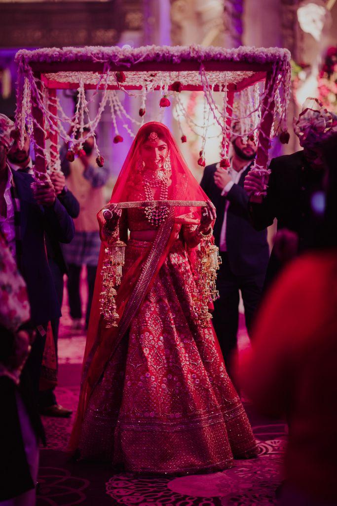 Photo of A bride in a red lehenga and a veil entering under a phoolon ki chaadar