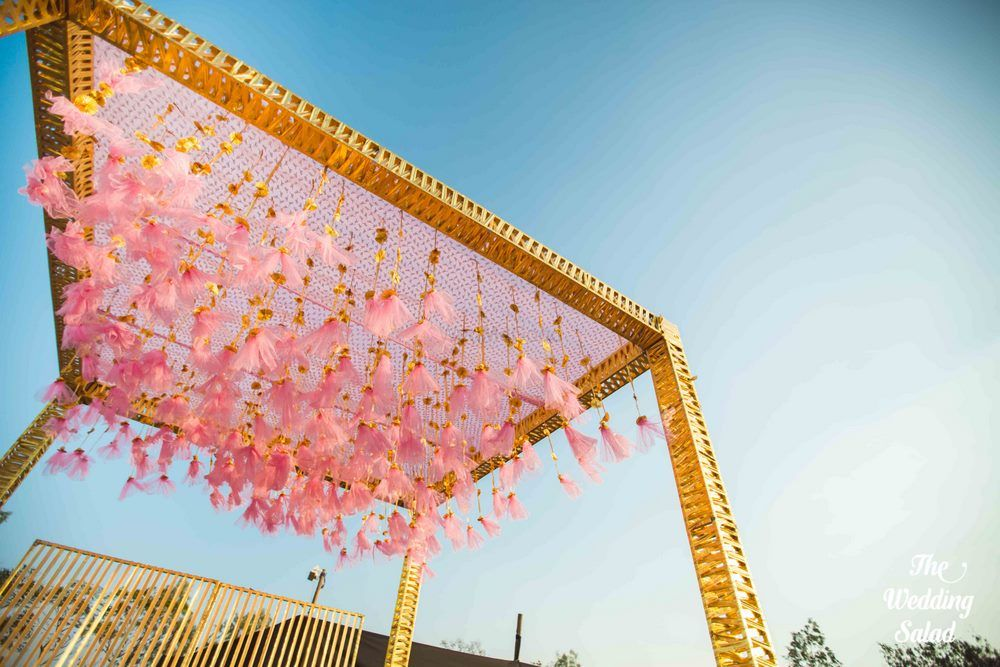 Photo of Light pink and gold mandap with hanging tassels
