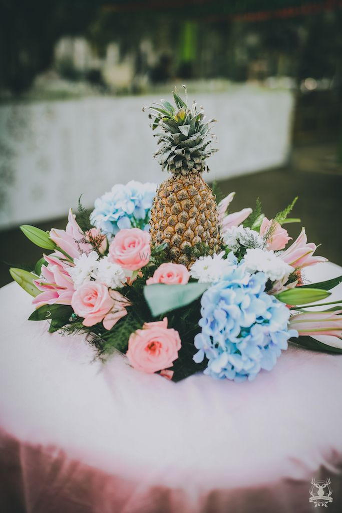 Photo of DIY centrepiece idea with pineapple and florals