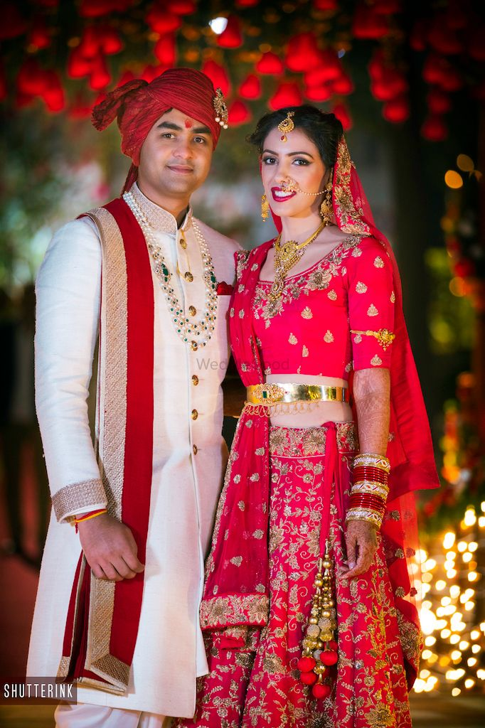 Photo of Red floral lehenga with gold waist belt