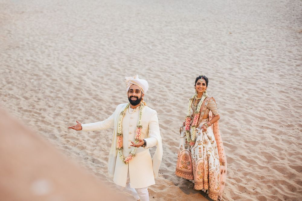 Photo of Matching bride and groom portrait against sand