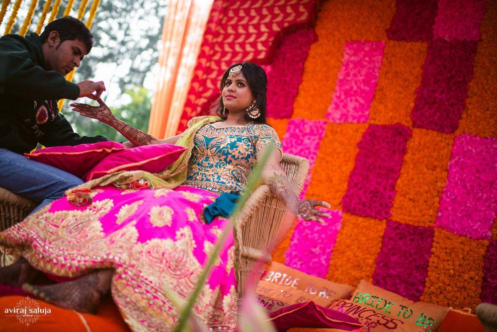 Photo of Bride putting mehendi in neon leheng