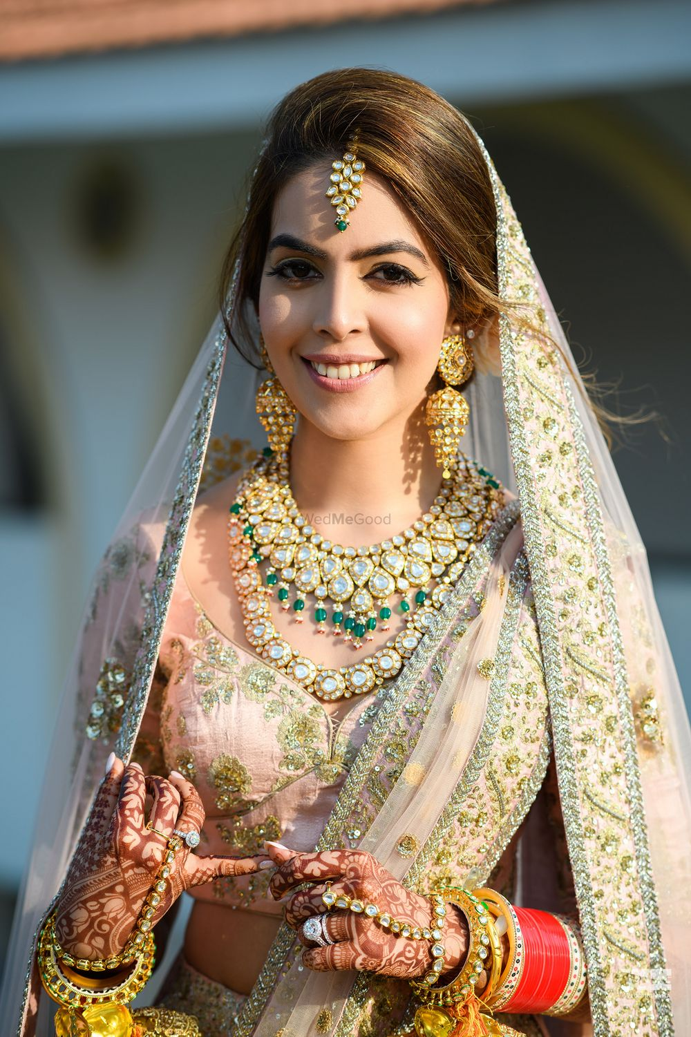 Photo of A close-up shot of a bride in a blush pink and gold lehenga for her wedding