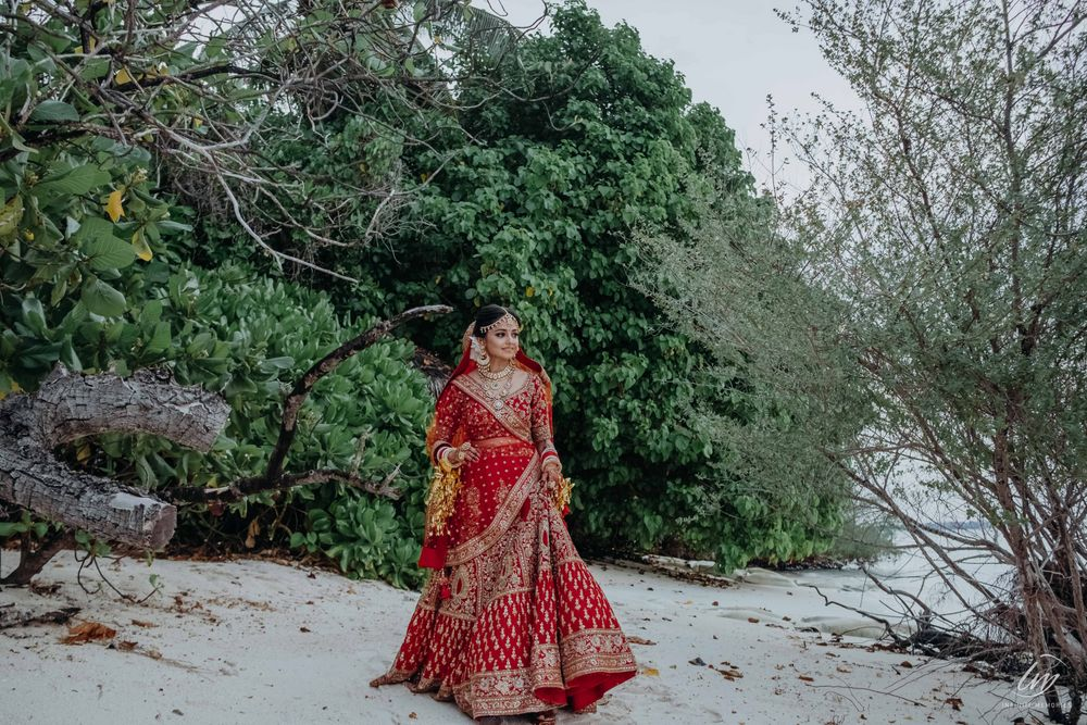 Photo of bride in red posing on her beach wedding