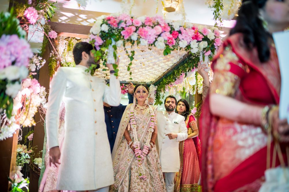 Photo of A bride in ivory lehenga enters under a phoolon ki chadar