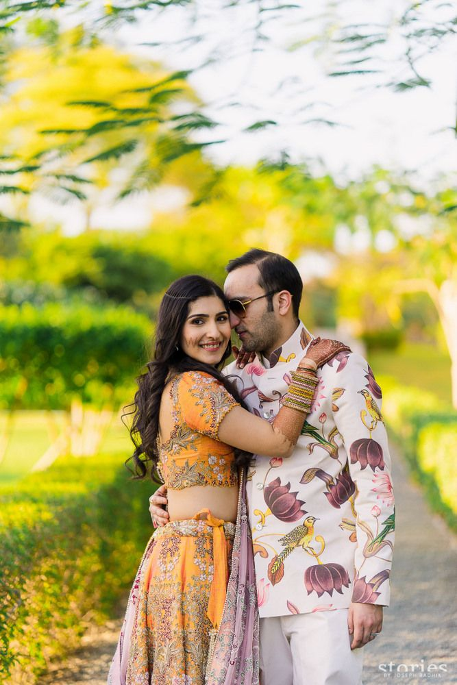 Photo of Bride and groom on mehendi function with floral print