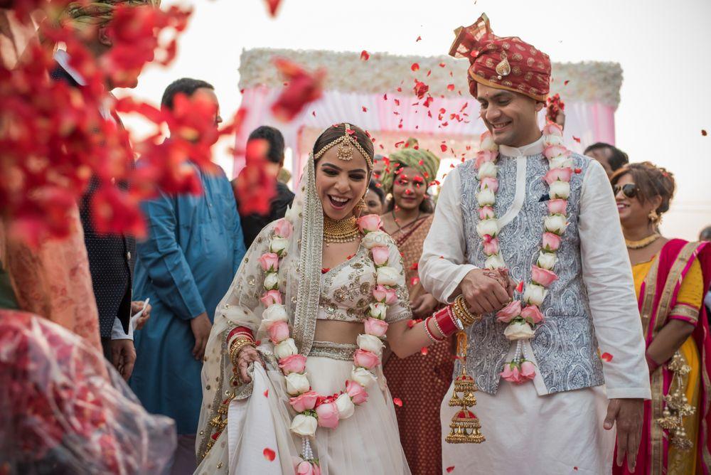 Photo of happy post wedding couple exit shot