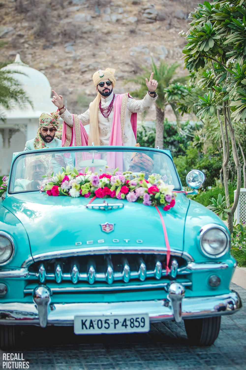 Photo of Groom dancing and entering in a vintage car