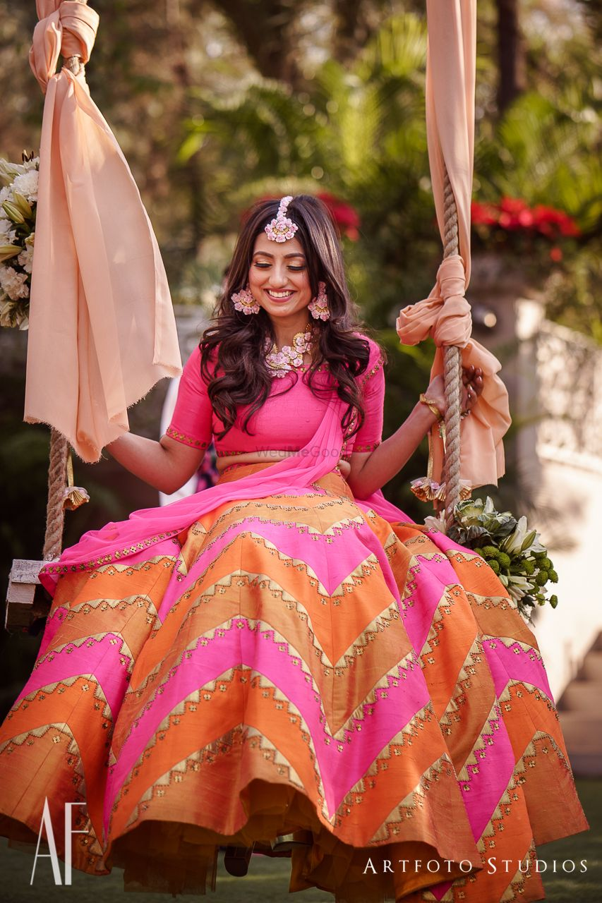 Photo of Bride on swing in orange and pink lehenga
