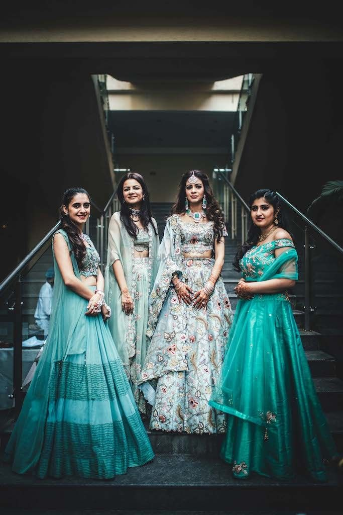 Photo of A bride in powder blue lehenga poses with her bridesmaids