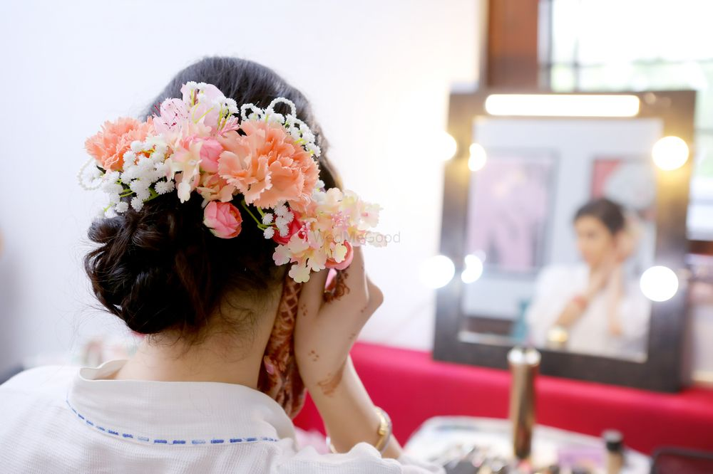 Photo of Pretty bridal bun with lots of florals