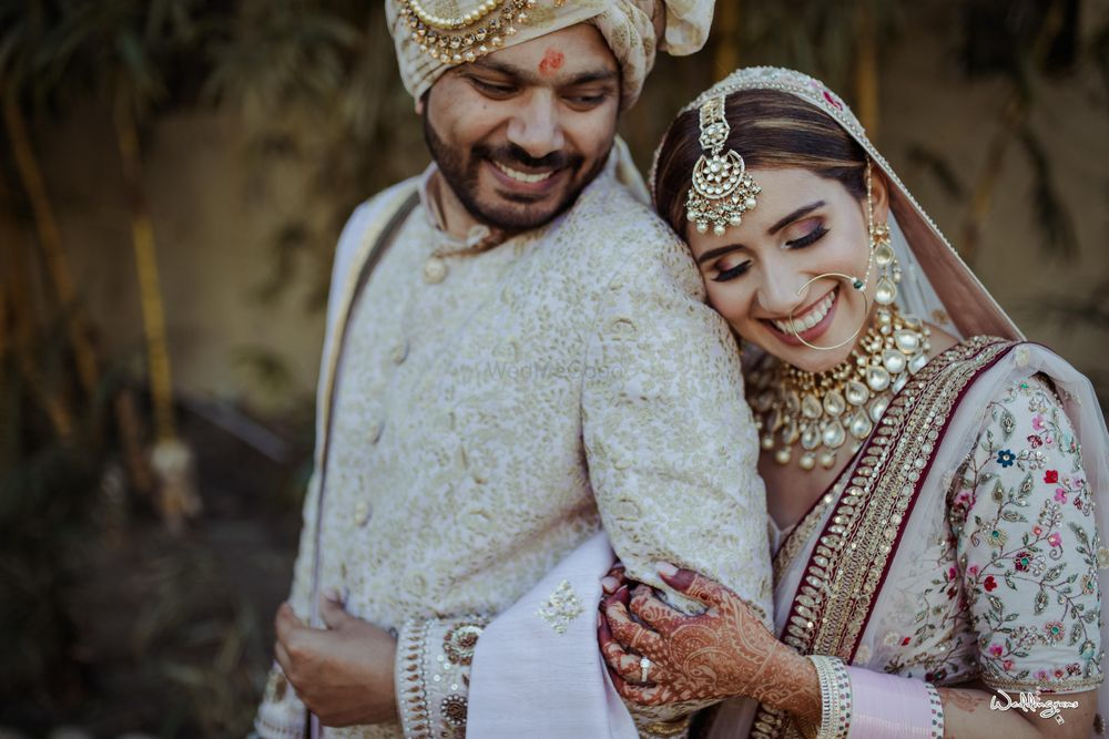 Photo of wedding day couple portrait with both wearing white indian outfits