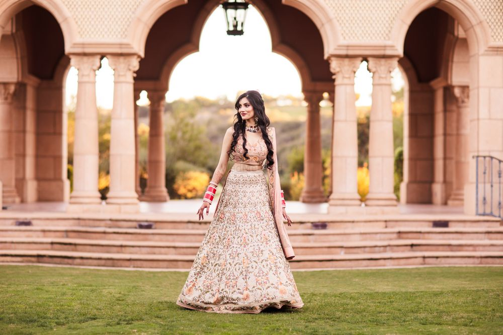 Photo of Bride in a subtle light pink lehenga for her engagement outdoors