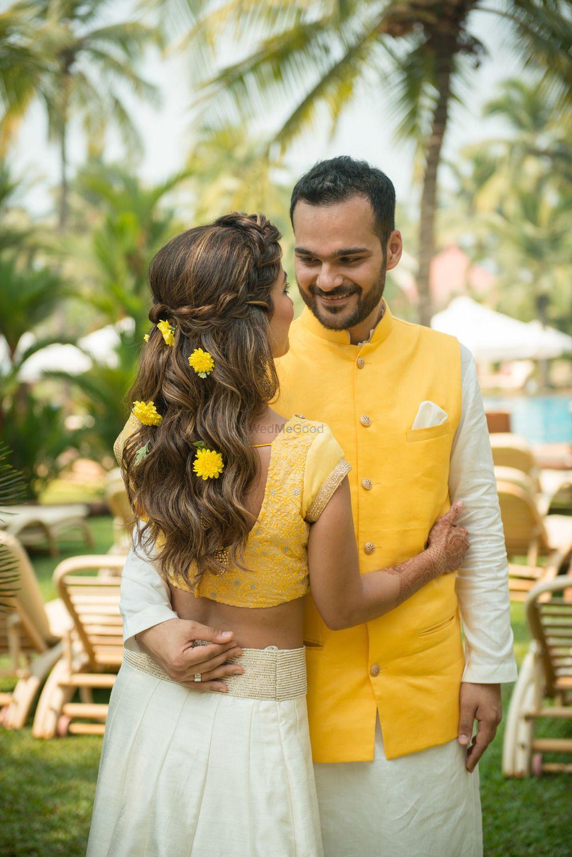 Photo of Matching bride and groom mehendi look with genda phool in hair