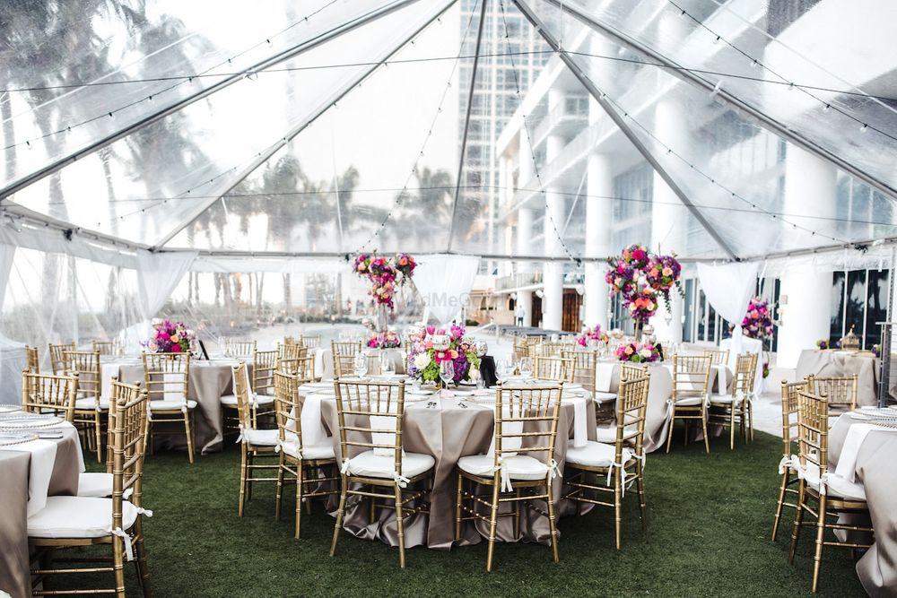 Photo of White and gold table setting with transparent tent