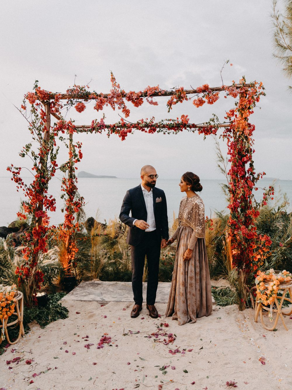 Photo of A couple shot candidly at their minimalist floral mandap