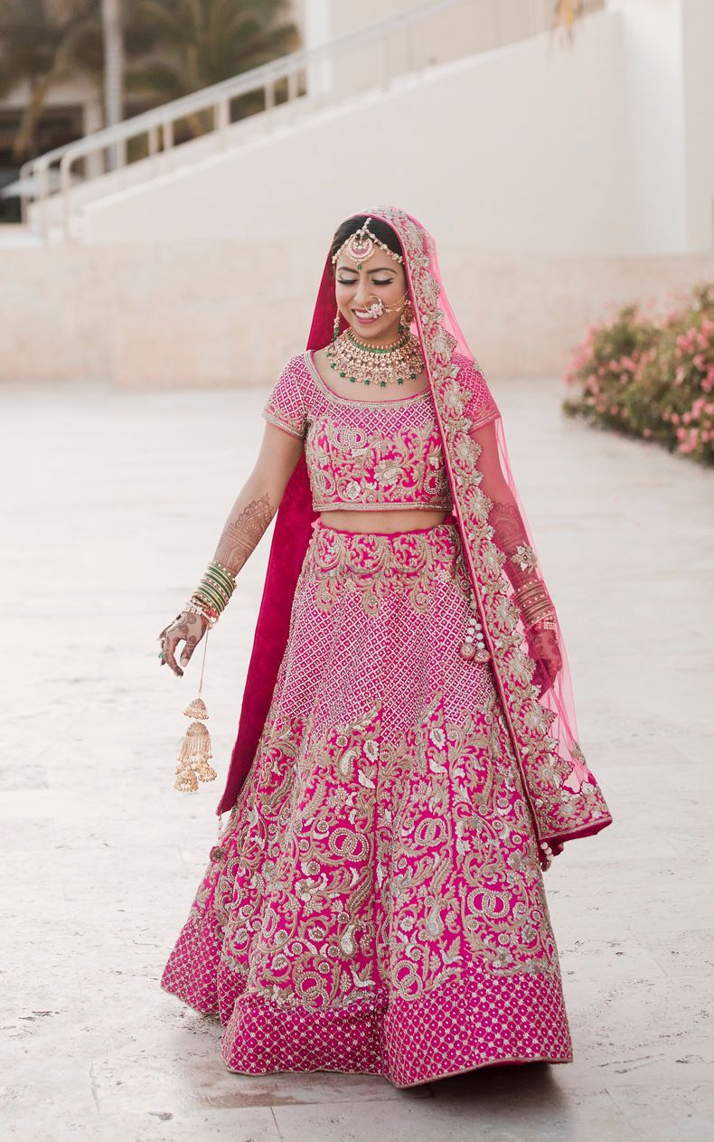 Photo of Bride in bright pink lehenga with embroidery all over it