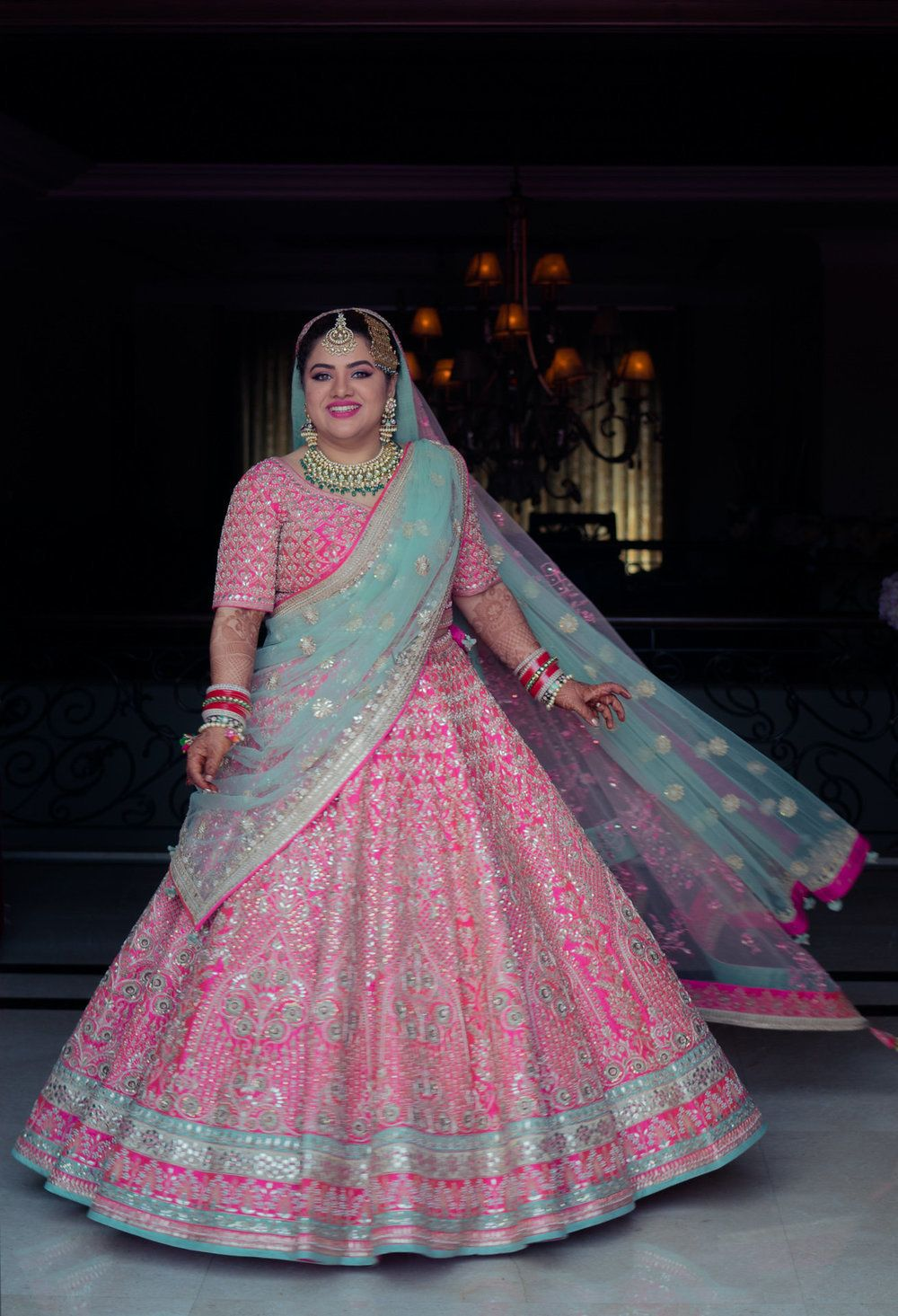 Photo of Twirling bride in pretty pink and turquoise lehenga